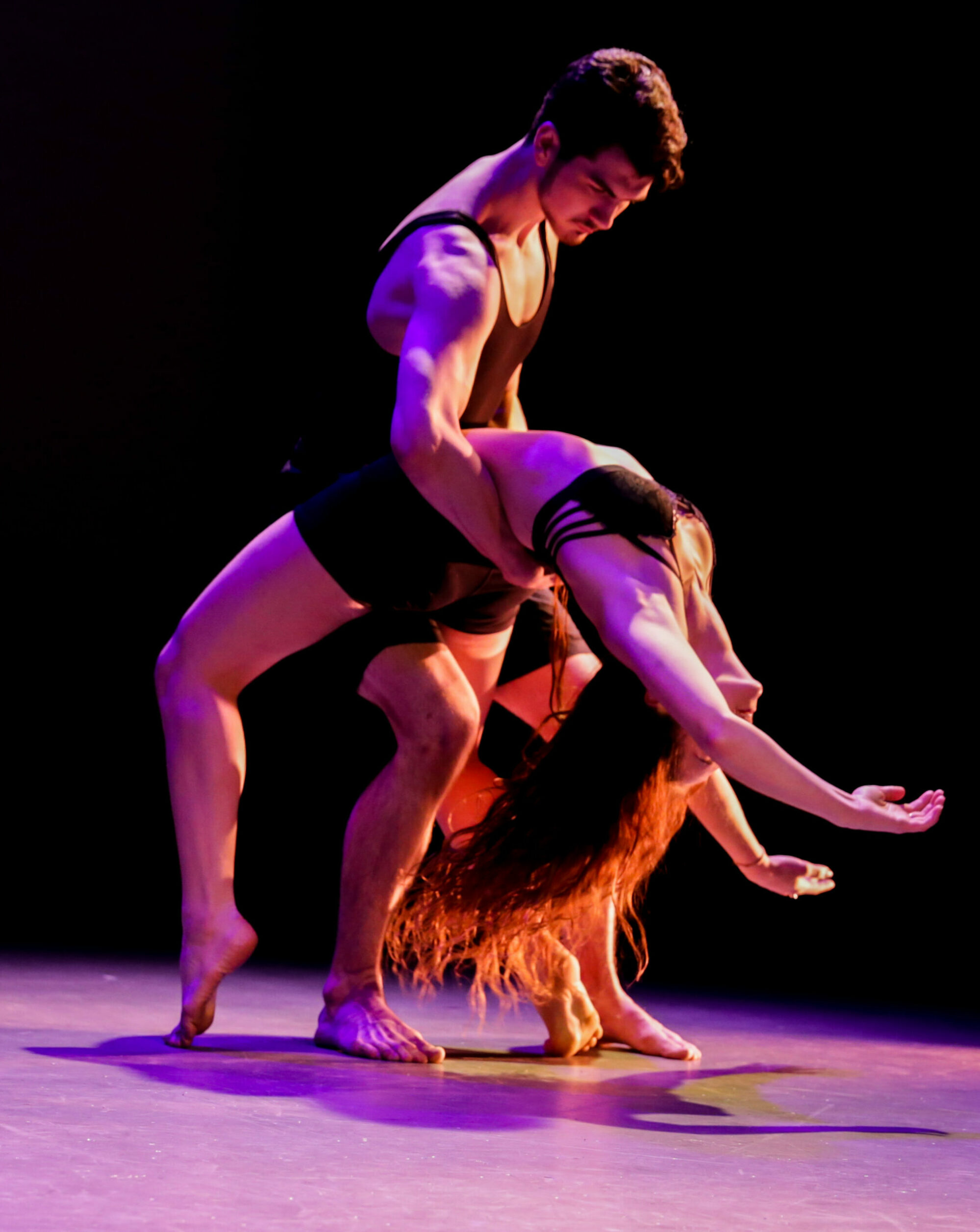 Two dancers performing a partnering routine during a live performance. They are wearing black costumes with purple light.