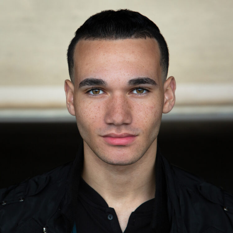 Jericho Lopez Headshot. He is wearing a black jacket with his hair pulled back. The background changes from dark to light